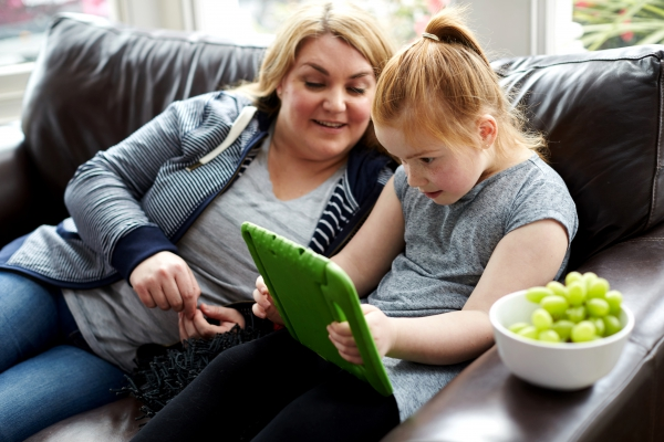 Mother helping daughter use iPad on sofa