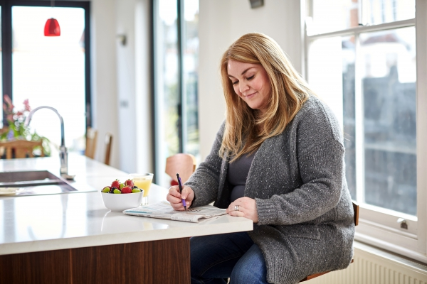 Woman writing in the kitchen